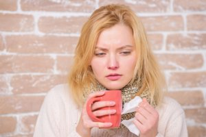 lady with cold symptoms drinking a hot drink and holding a tissue