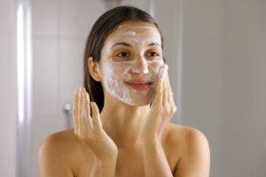 woman washing face foaming soap scrubbing skin