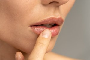 Close up of woman applying moisturizing nourishing balm to her lips with her finger.