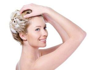 Beautiful smiling young woman washing her hair with shampoo