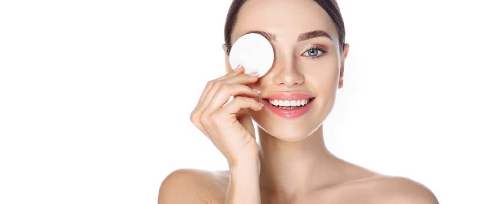 Makeup remove, skin care. Smiling woman with cosmetic cotton pad near her face, concept remove makeup and clean skin