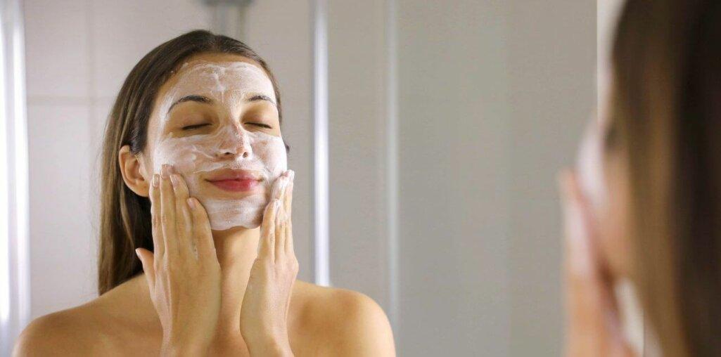 Skincare woman washing face foaming soap scrubbing skin. Face wash exfoliation scrub