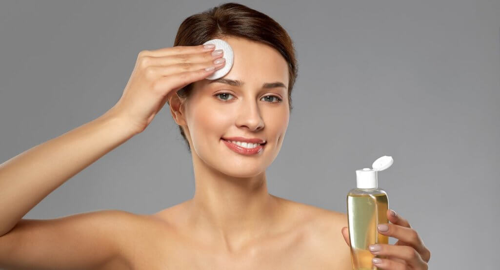 smiling young woman with toner or cleanser and cotton pad cleansing face over grey background