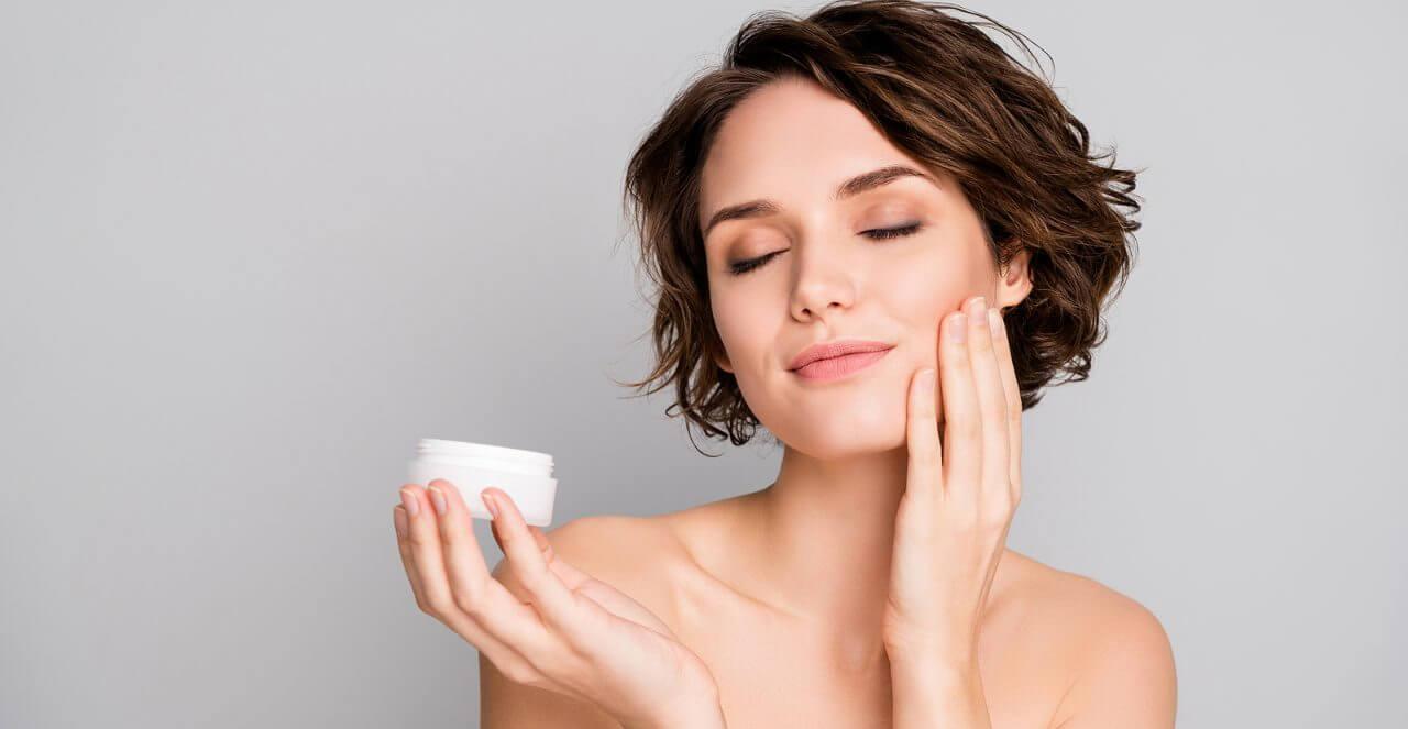 lady short bob hairdo hold new daily night treatment cream jar apply cheekbone eyes